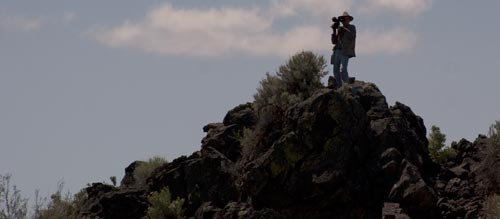 Anders Tomlison filming from atop a volcanic outcropping in Lava Beds National Monument.