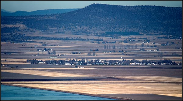 With the opening of the 1922 homesteads, plans were drafted  by the Reclamation Service for the town site of Tulelake.  Years passed before the first public auction of lots  was held on April 15th, 1931.     view from schonchin butte of tulelake, ca.  photo by anders tomlinson.