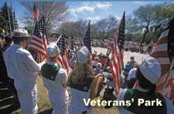 Tulelake $H members hold flags as a backdrop to Bucket Brigade speakers at Veterans' Park, Klamath Falls, oregon. May 7th, 2001. Photo by Anders Tomlinson.